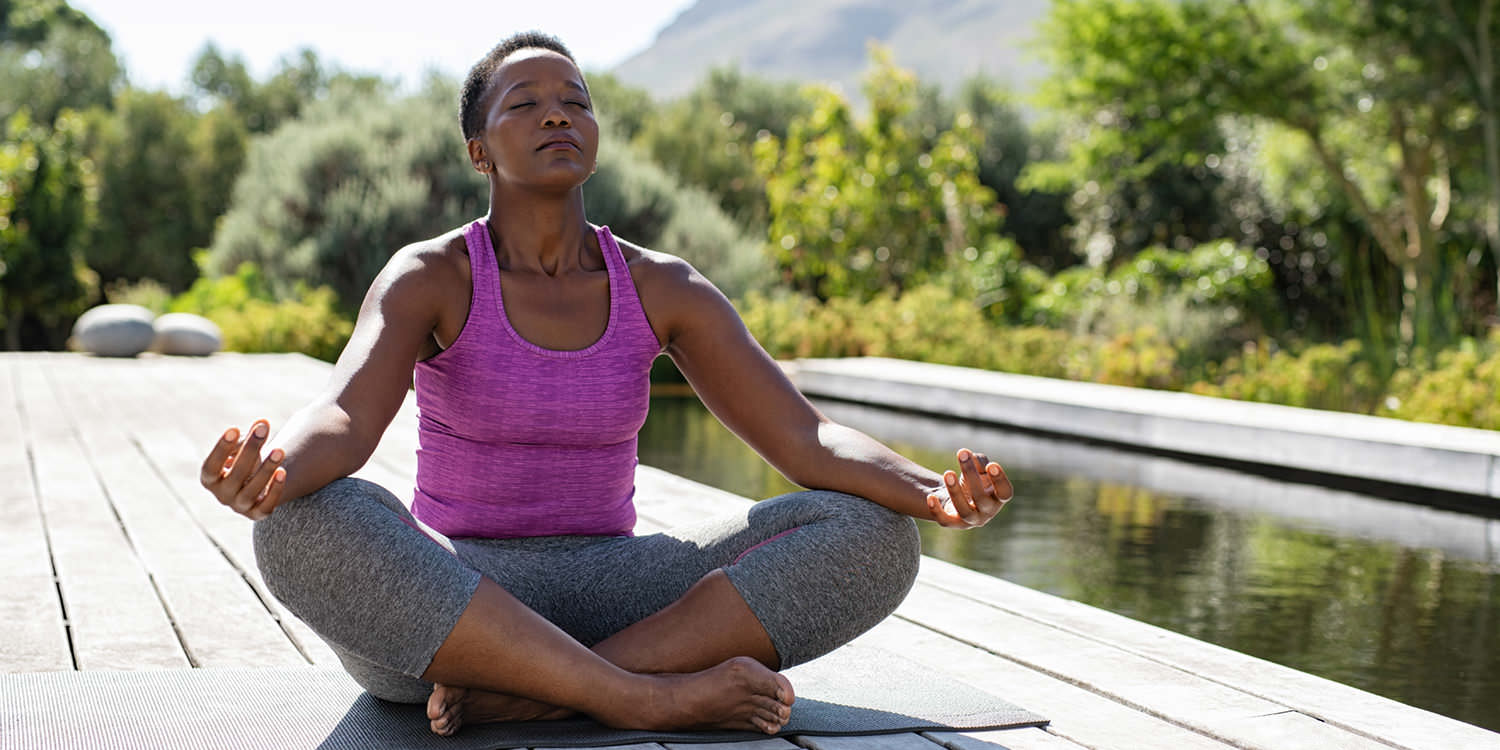 A middle-aged black woman wearing yoga clothes is sitting on a dock meditating.