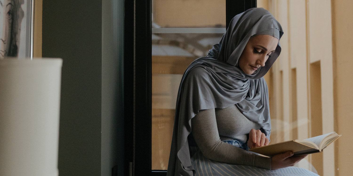 A middle Eastern woman wearing a hijab is sitting by a window and reading.