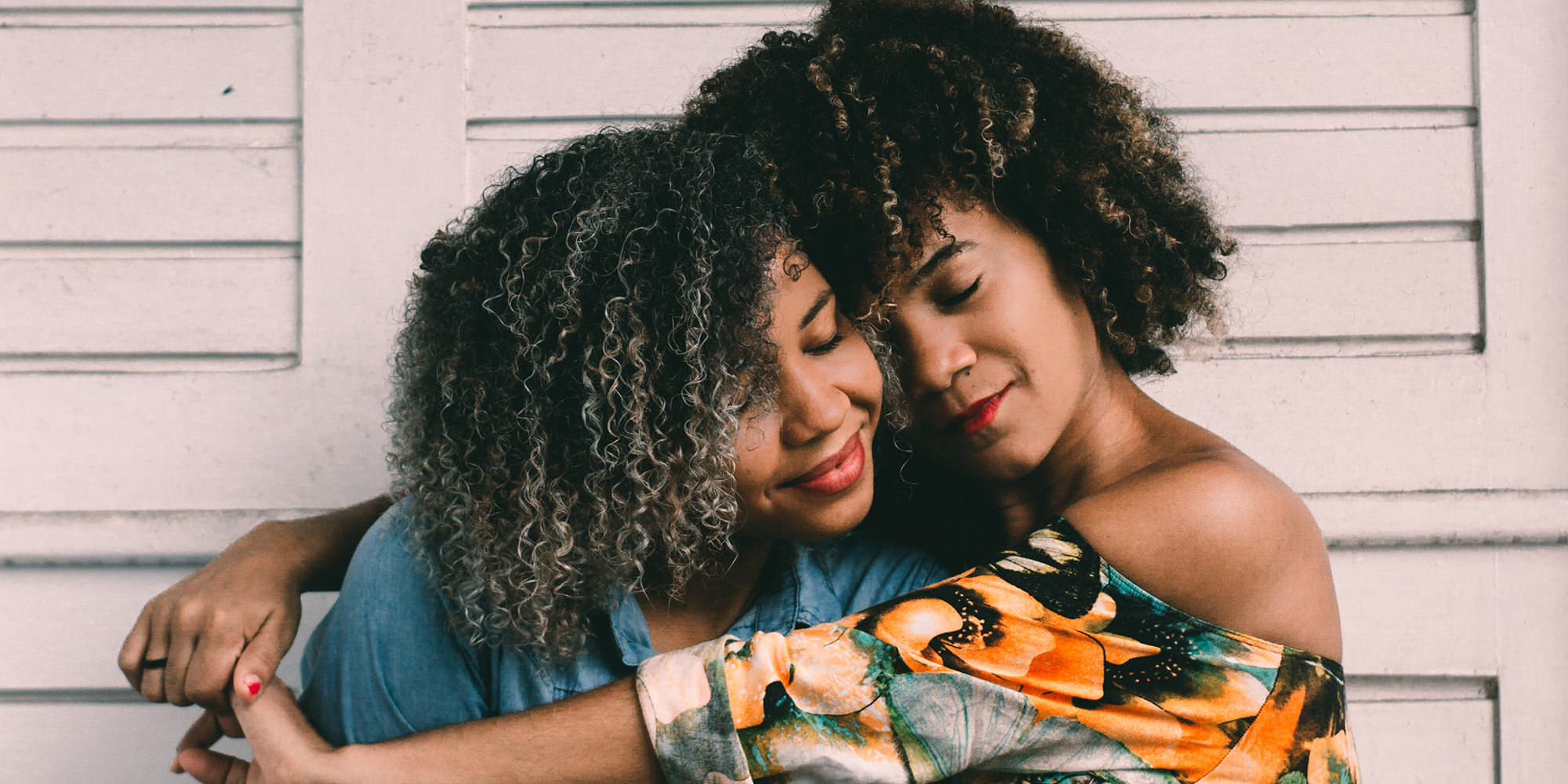Two young a black women with long curly hair sitting together. The older one is hugging the younger one, who looks to be in her teens. They look like they might be sisters.