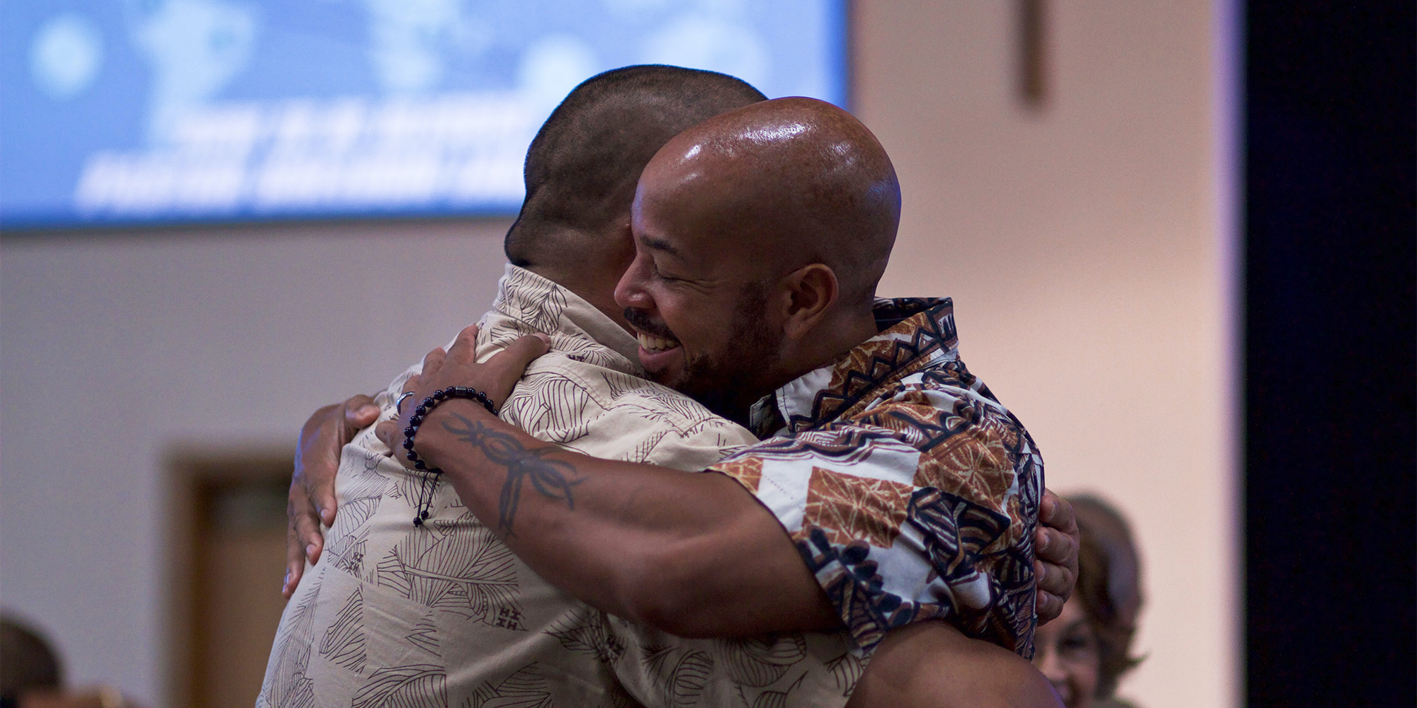 Two African American men at a public event, giving each other a hug.