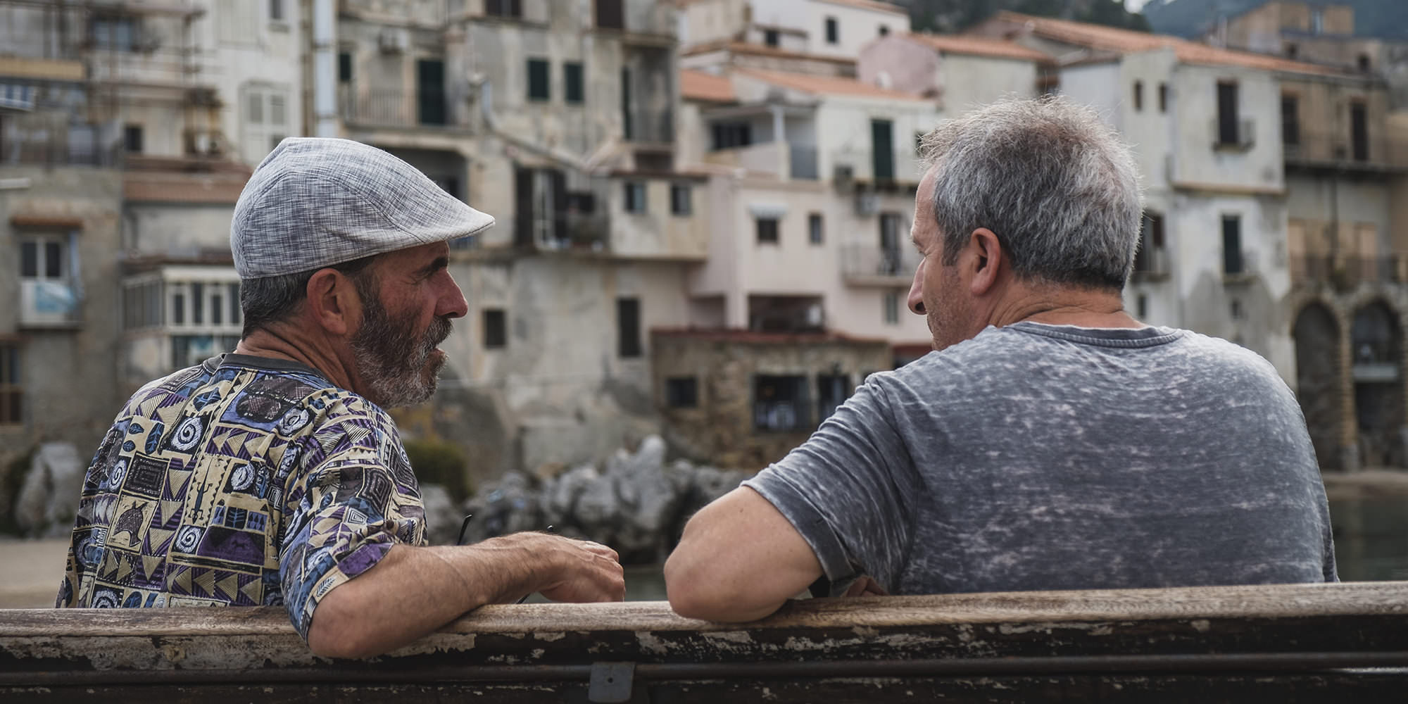 Two older white men sitting together on a bench, engaging in conversation. Relationships between friends are also important for bipolar disorder.