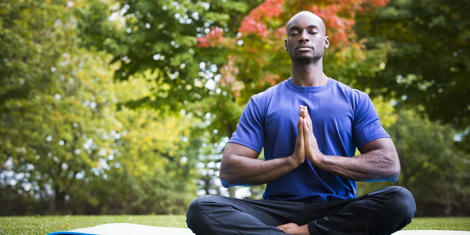 A black man in his late twenties or thirties is sitting outdoors on a yoga mat, engaged in meditation.