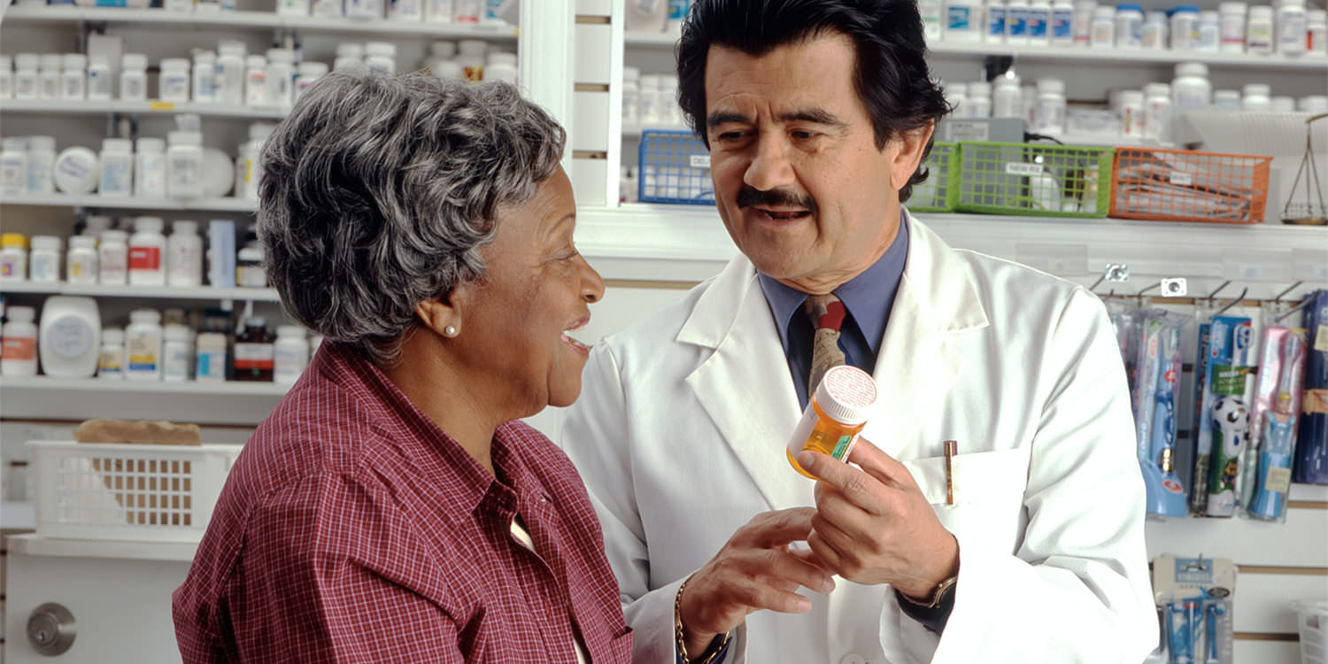 An older black woman is talking to her pharmacist about her medication.