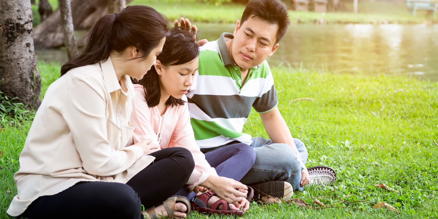 An adolescent east Asian girl is sitting in a public park and looking downcast, implied here to be due to feeling a lack of independence with bipolar disorder. Her parents are on either side of her and are trying to comfort her.