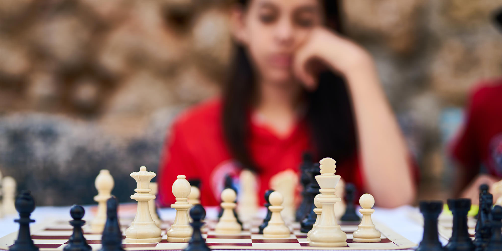 A young woman with brown skin and dark hair playing a game of chess.