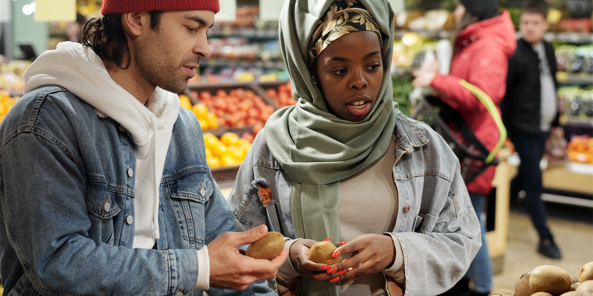 Nutrition is another core component of physical health. Here, a young Muslim couple select fruit at the grocery store.