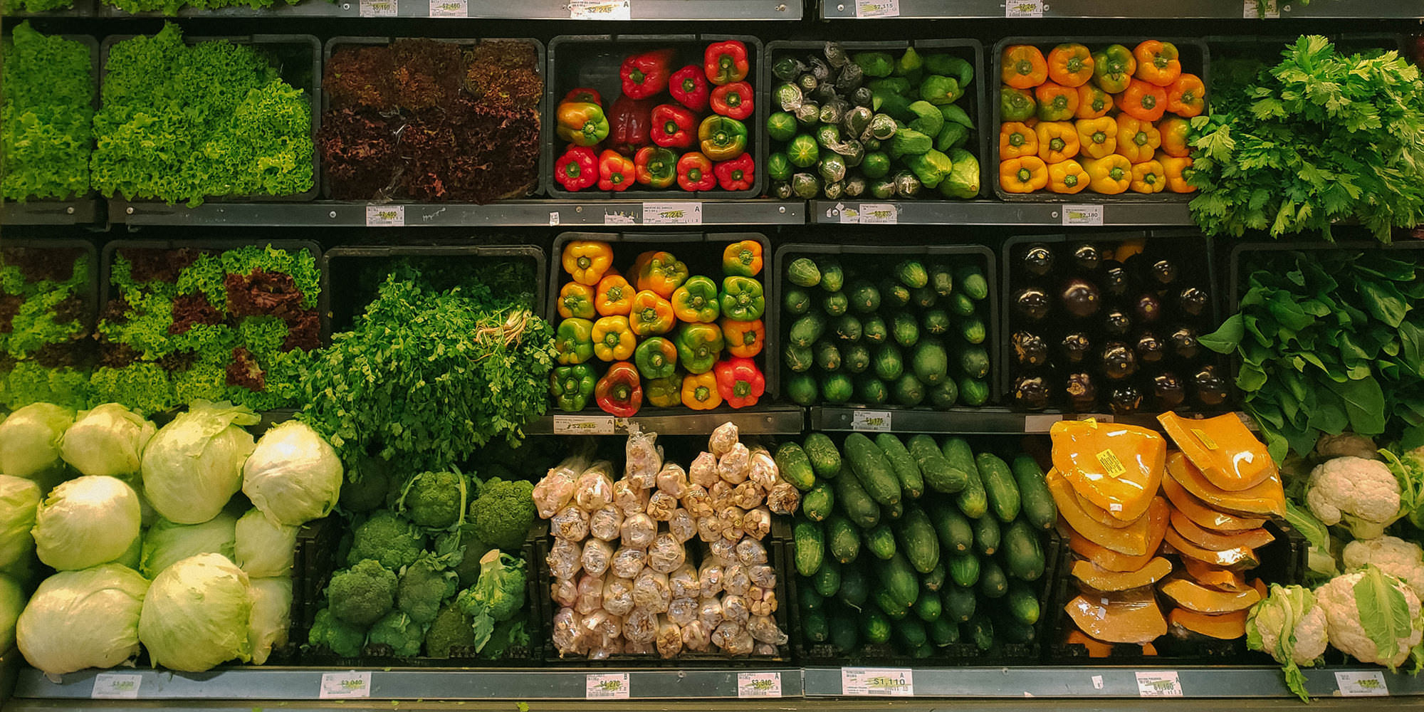 An organized grocery store display of healthy food: cucumbers, peppers, eggplant, lettuce, cauliflower, and more.