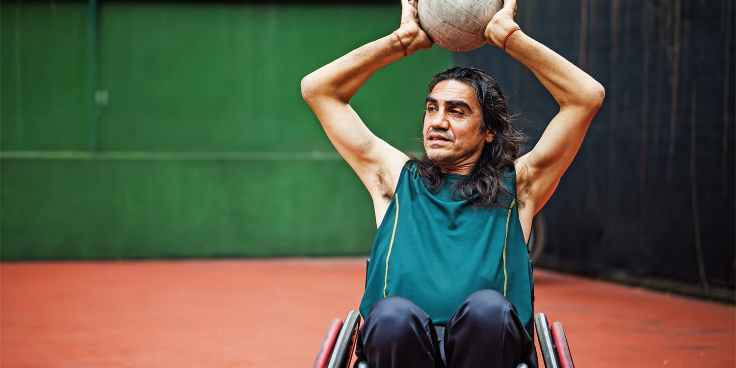 Exercise is a core component of physical health, for those with and without bipolar disorder. In this picture, an Indigenous man in a wheelchair is playing volleyball or something similar inside a gymnasium.