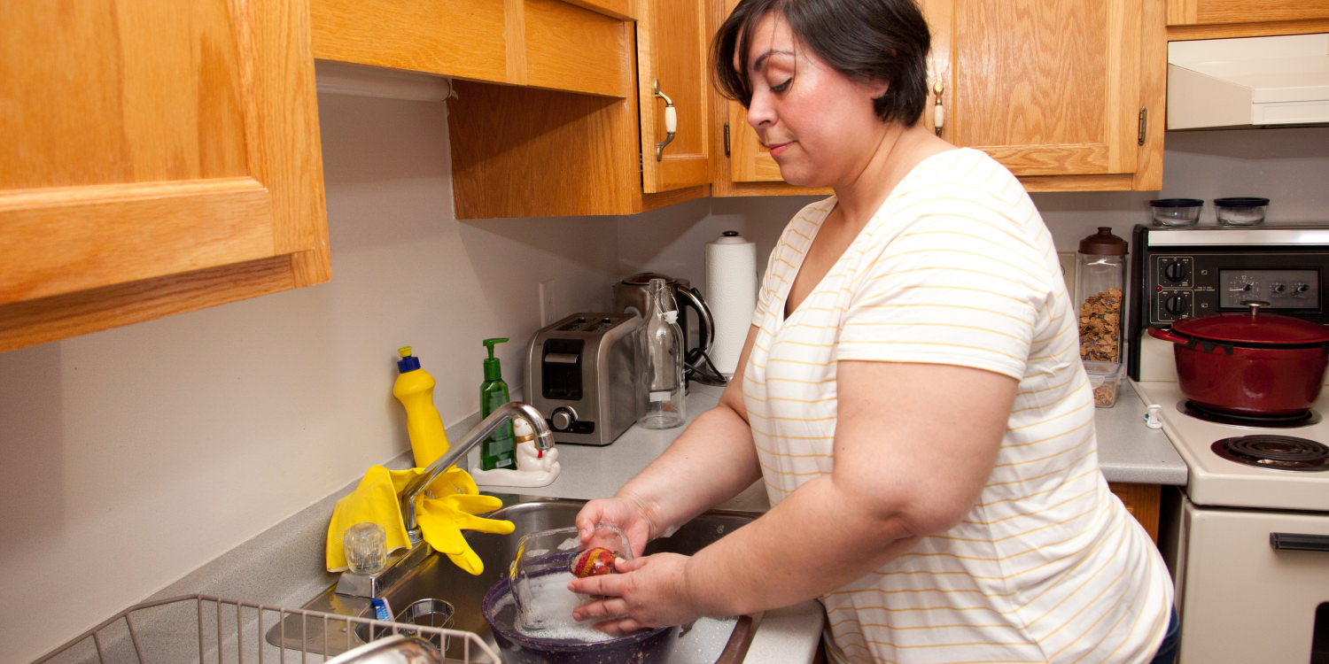 A white woman is doing dishes. When managing your home with bipolar disorder, it can help to set small goals for yourself.