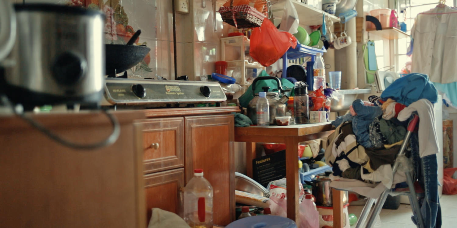 A kitchen counter with lots of dishes and food ingredients left out.