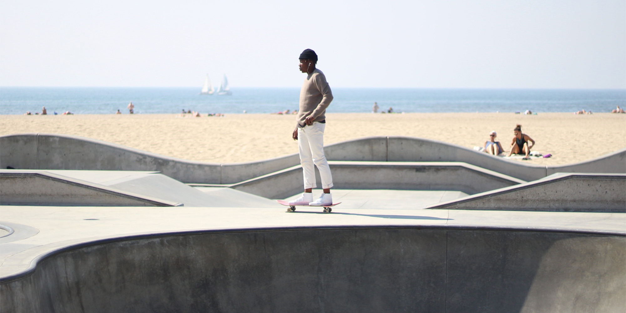 A young black man is skateboarding at a skate park by the beach. The sandy shores and the ocean can be seen in the background.