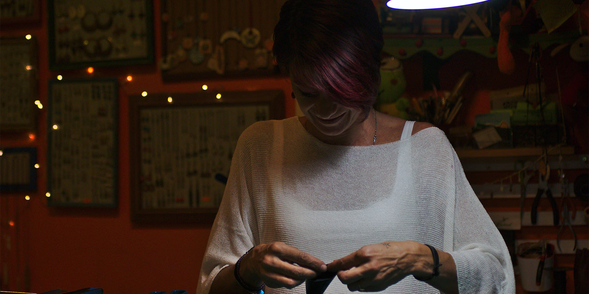 A middle aged-white woman with short dark hair is standing in a dimly lit room holding what looks like it could be a wallet or a coin pouch.