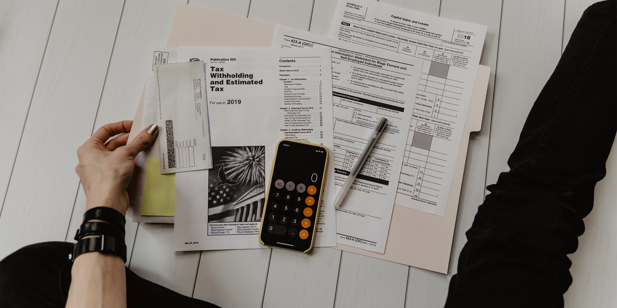A close-up of someone sitting on the floor, with an arrangement of financials and tax return documents and their phone set to the calculator mode. It's a close-up showing just their arm and legs. They have white skin and are wearing a black leather bracelet, nail polish, and black skinny jeans.