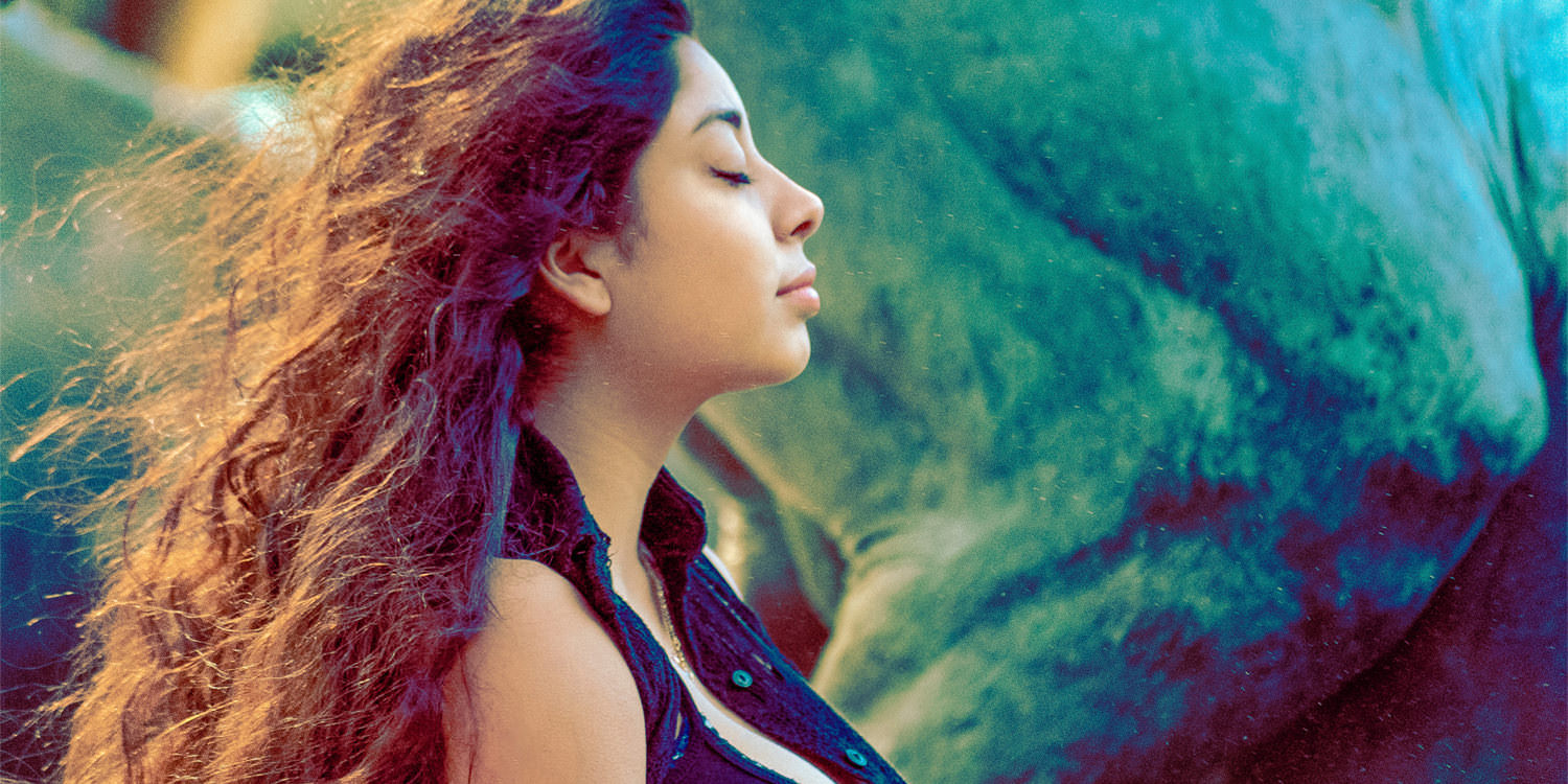 A young woman with dark curly hair and light brown skin standing with her eyes closed and looking at peace. The wind is blowing through her hair and the sun is glowing on her hair.
