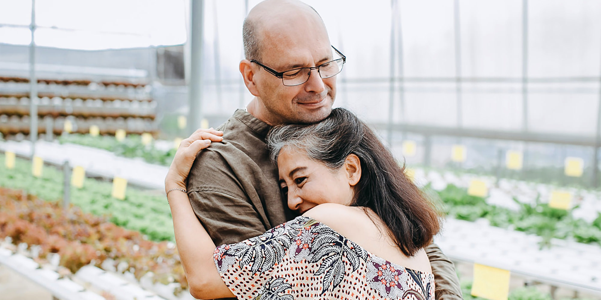 Sexual health is an important component of physical health, too! In this picture, a middle-aged couple - a white man and an Asian woman - are locked in an embrace.