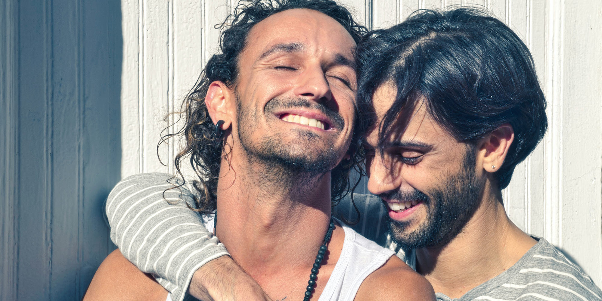 A middle eastern man has his arm around a white man. They look joyful and are sitting in the sun.