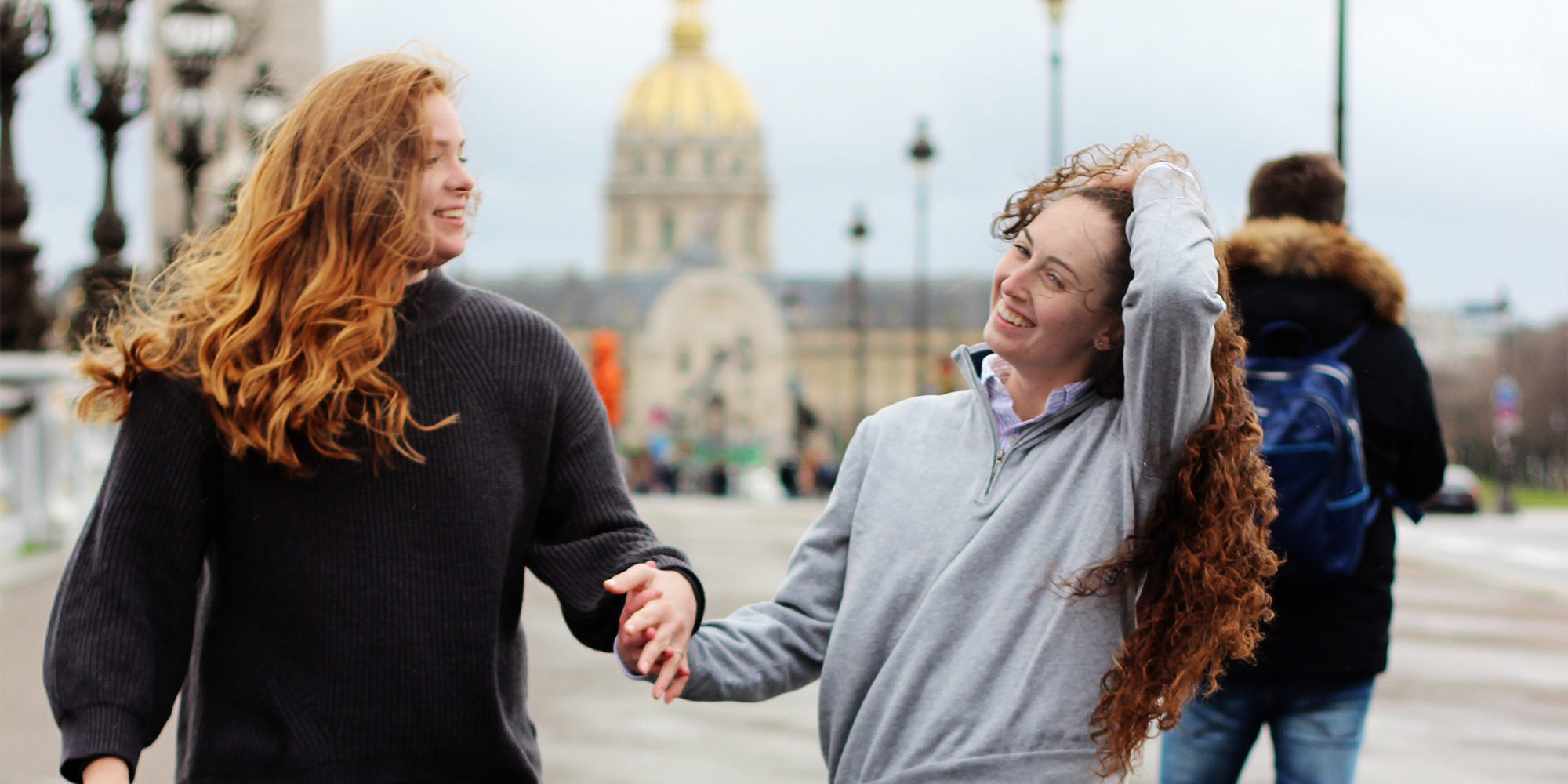 Two young white women with long red hair are holding hands in a public space. The woman on the right is running her hands through her hair and smiling bashfully while the woman on the left looks at her with amusement.