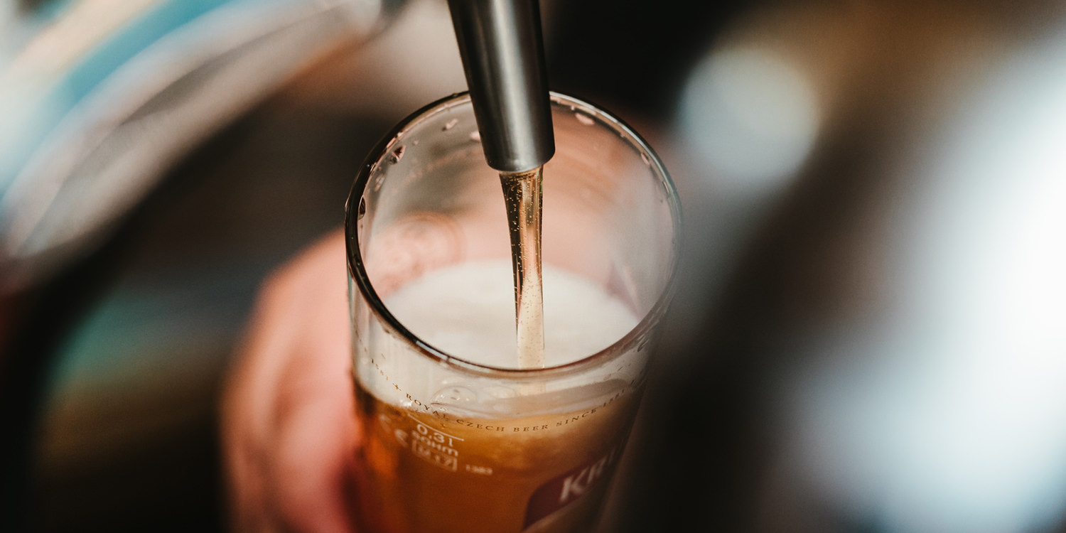 A glass of beer being filled from the tap.
