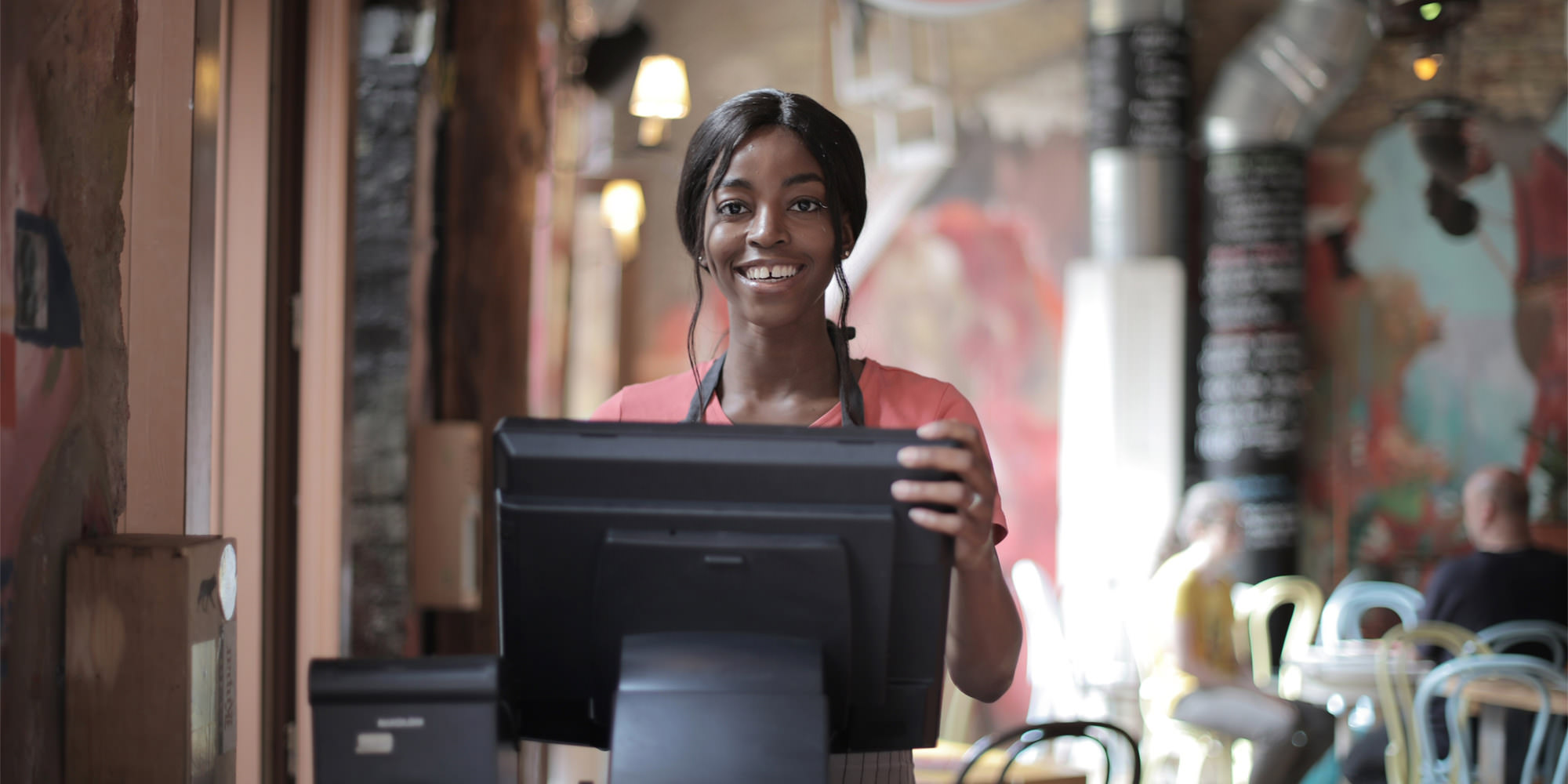 A young black waitress is standing at the cash register and smiling.